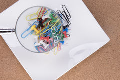 Lupa sobre paperclips y pernos de dibujo coloridos Fotografía de archivo