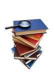 Lupa sobre a pilha de livros Fotografia de Stock Royalty Free