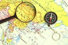 Lupa, um compasso e um mapa Imagens de Stock Royalty Free