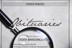 Lupa y anuncio de los obituarios en el periódico Foto de archivo