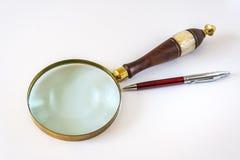 Lupa y bolígrafo Pen On White Backgroundr Imágenes de archivo libres de regalías