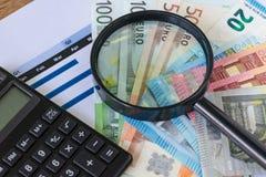 Lupa y calculadora negra en la pila de billetes de banco euro Imágenes de archivo libres de regalías