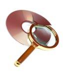 Lupa y CD roto Imagenes de archivo