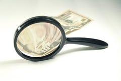 Lupa y dinero Imagen de archivo libre de regalías