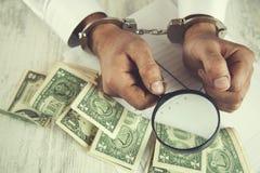 Lupa y dinero de la mano del hombre fotos de archivo