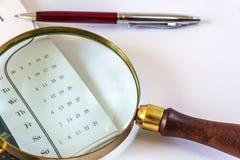 Lupa y el calendario de Pen Are Lying On The Fotografía de archivo