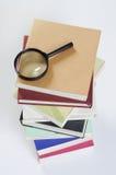 Lupa y libros de la visión superior Imagen de archivo libre de regalías