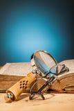 Lupa y vidrios del libro en la tabla de madera Imagen de archivo