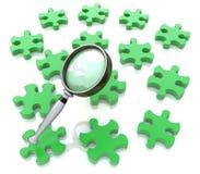 Lupe auf dem grünen Puzzlespiel Lizenzfreies Stockfoto
