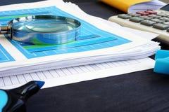Lupe auf Dokumenten mit Geschäftsdiagrammen und Finanzinformationen Innenrevision lizenzfreie stockfotografie