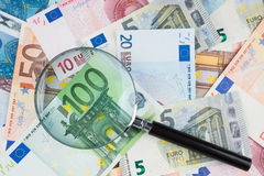 Lupe auf Eurogeld Stockfotografie