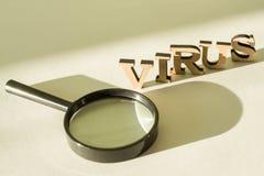 Lupe auf weißem Hintergrund mit dem Wort VIRUS Lizenzfreie Stockfotografie