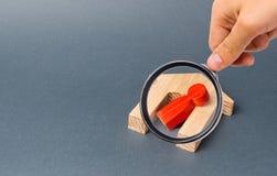Lupe betrachtet eine rote Fig?rchen eines Mannes und ein gefallenes Haus auf einem grauen Hintergrund Unfall oder Unfall stockfoto