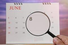 Lupe in der Hand auf Kalender können Sie achten Tag von schauen Lizenzfreie Stockfotografie