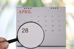 Lupe in der Hand auf Kalender können Sie achtundzwanzig d schauen Stockfotos