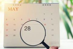 Lupe in der Hand auf Kalender können Sie achtundzwanzig d schauen Lizenzfreie Stockbilder