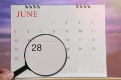 Lupe in der Hand auf Kalender können Sie achtundzwanzig d schauen Lizenzfreie Stockfotos