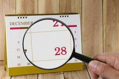 Lupe in der Hand auf Kalender können Sie achtundzwanzig d schauen Stockbild