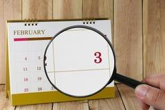 Lupe in der Hand auf Kalender können Sie dritten Tag von m schauen Stockbilder