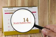 Lupe in der Hand auf Kalender können Sie Weltdiabetes schauen Lizenzfreie Stockbilder