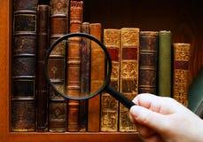 Lupe in der Hand und alte Bücher Stockbild