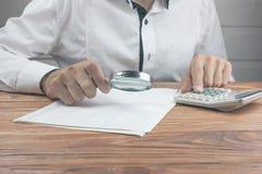 Lupe mit Finanzdokumenten und Taschenrechner lizenzfreies stockbild