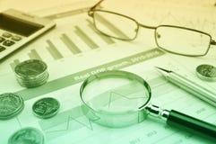 Lupe, Stift, Münzen, Taschenrechner und Gläser auf Wachstumsfinanzdiagramm, GeschäftserfolgKonzept stockfotografie