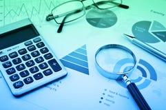 Lupe, Taschenrechner, Stift und Gläser auf Diagramm-, Blauem und Grünemton des betrieblichen Gesamtbudgets, Finanzerfolgskonzept lizenzfreie stockfotos