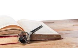 Lupe und alte Bücher lokalisiert Stockfotografie
