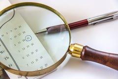 Lupe und Kugelschreiber auf Kalender Stockfoto