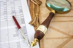 Lupe und Pen Lying On Financial Document auf dem offenen ledernen Ordner Lizenzfreie Stockfotos