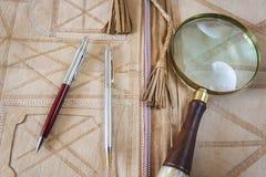 Lupe und zwei Stifte auf ledernem Ordner Stockfotografie