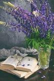 Lupine e livro velho Ainda a vida com roxo floresce o ramalhete no vaso Imagem de Stock