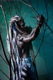 Lupo mannaro muscolare del ritratto con i dreadlocks fra i rami di Immagini Stock