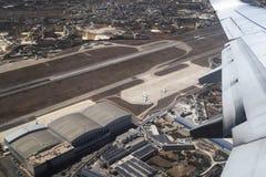 LUQA,马耳他- 2016年8月06日:马耳他机场跑道和大厦鸟瞰图  被射击的乘的里面离去的商用飞机 图库摄影