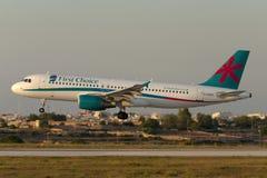 Luqa, Malta - 5 de julho de 2007: Aterrissagem do por do sol A320 Imagens de Stock