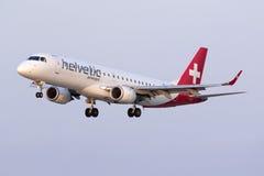 Luqa, Malta 10 July 2015: Helvetic ERJ-190 landing. Helvetic Airways Embraer 190LR (ERJ-190-100LR) on finals runway 31, arriving from Zurich as a Swissair royalty free stock images
