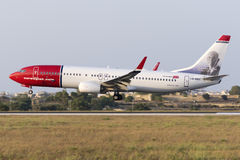 Luqa, Malta 10 July 2015: Norwegian 737 landing. Norwegian Air Shuttle Boeing 737-8JP on finals runway 31 in the late evening low light. The color scheme on Royalty Free Stock Photography