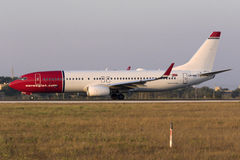 Luqa, Malta 8 July 2015: Norwegian 737 on the runway. Norwegian Air Shuttle Boeing 737-8JP departing back to Oslo in the late evening warm light Stock Images