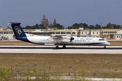 Luqa, Malta 11 July 2015: Olympic DHC-8 landing. Olympic Bombardier DHC-8-402 Q400 is seen landing runway 13, arriving from Athens, Greece Royalty Free Stock Photo