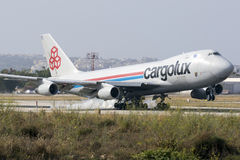 Luqa, Malta 24 June 2015: Cargo plane 747 landing. A Cargolux Boeing 747-400 landing runway 13 in the mid afternoon. The 747 is the original Jumbo jet and first Royalty Free Stock Images