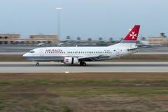 Luqa, Malta 21 June 2005: 737 landing. Air Malta Boeing 737-33A [9H-ADH] landing runway 32 after sunset. Later sold to Air New Zealand Stock Photo