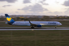 Luqa, Malta - 20 September 2015: 757 accelerating. Condor (Thomas Cook) Boeing 757-330 taking off runway 31 after sunset. Panning effect by a low shutter speed Stock Photos