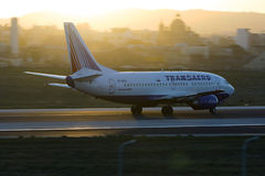 Luqa, Malta - 20 September 2015: 737 accelerating. Transaero Airlines Boeing 737-5K5 taking off runway 31 during sunset. Panning effect by a low shutter speed Stock Images