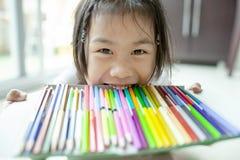 Lura asiatiska barn och magasinet av färg rita arkivfoto