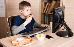 Lura att äta pizza och att surfa på internet eller att spela videospel arkivbilder