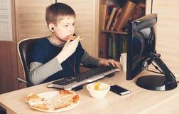 Lura att äta pizza och att surfa på internet eller att spela videospel Royaltyfri Bild