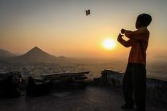 Lura att flyga hans drake på solnedgången på Pap Mochani Gayatri Temple, Pushkar, Rajasthan, Indien Arkivfoto