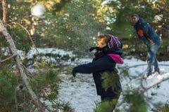 Lura att kasta ut snöbollar i backen Royaltyfria Bilder