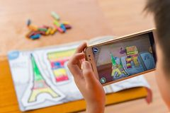 Lura att spela ökade popup målningar för verklighet av den fyllda bågen av Triumph & Eiffeltorn via mobil Royaltyfri Foto